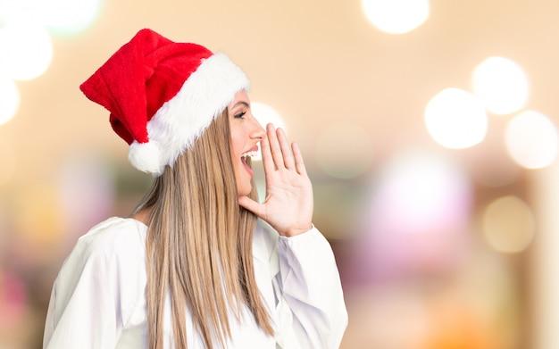 Het meisje dat met kerstmishoed met mond wijd open over ongericht achtergrond schreeuwt