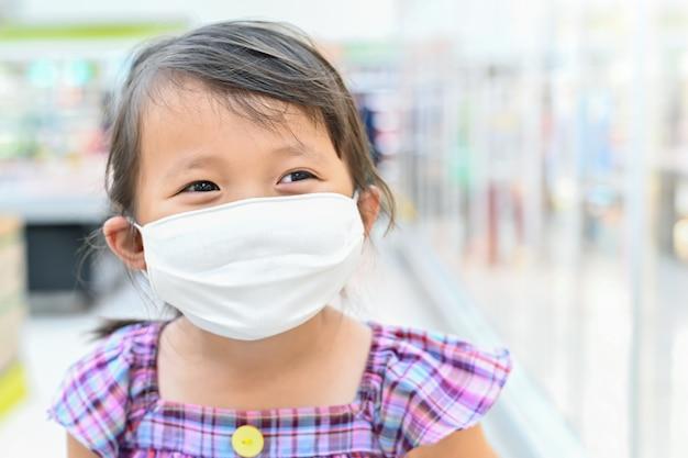 Het meisje dat stoffenmasker draagt beschermt zichzelf tegen coronavirus
