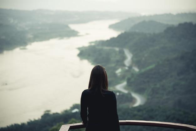 Het meisje dat van azië zich bij het terras bevindt dat aan de mening van de bergrivier kijkt