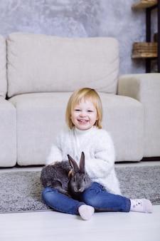 Het meisje dat van de blondebaby in witte sweater en jeans glimlacht die thuis op het tapijt dichtbij de bank zitten.