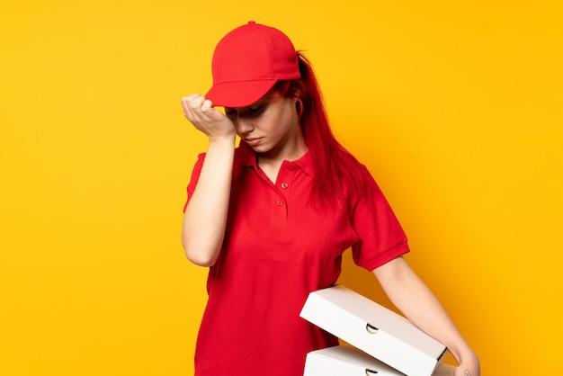 Het meisje dat van de pizzakoerier een pizza over geïsoleerde muur met hoofdpijn houdt