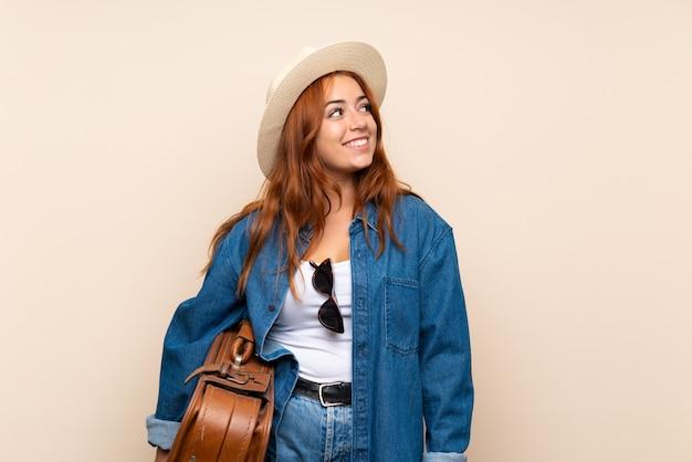Het meisje dat van de roodharigereiziger met koffer omhoog terwijl het glimlachen kijkt