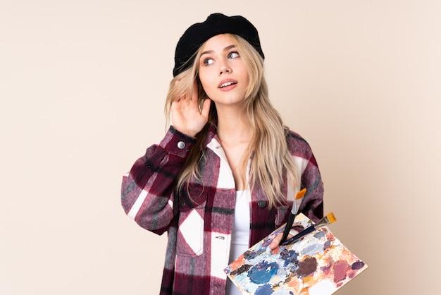 Het meisje dat van de tienerkunstenaar een palet houdt dat op blauw wordt geïsoleerd