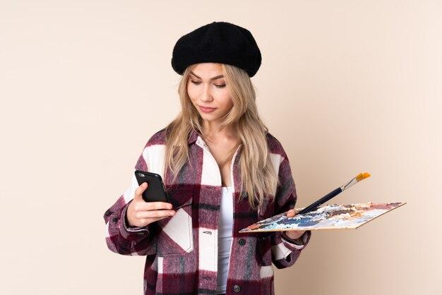 Het meisje dat van de tienerkunstenaar een palet op de blauwe weg te nemen koffie van de muurholding en mobiel houdt
