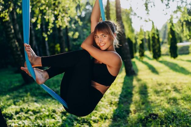 Het meisje dat van nice vliegyoga in park in openlucht doet. gelukkig naar de camera kijken