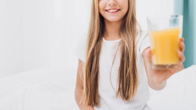 Het meisje dat van vooraanzichtsmiley een glas jus d'orange houdt