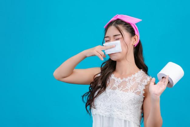 Het meisje dat witte pyjama's draagt, voelt zich niet comfortabel. gebruik weefsel om haar neus over een blauw te vegen.