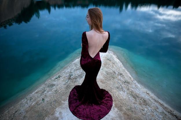 Het meisje dat zich op de rotsen dichtbij het meer bevindt. berglandschap, berglandschap in oost-europa.