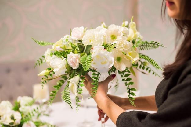 Het meisje de bloemist maakt een boeket bloemen, de bloemist doet een boeket.