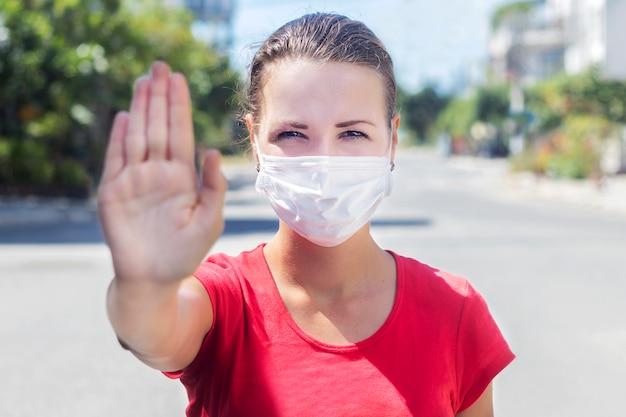Het meisje, de jonge vrouw die in beschermend steriel medisch masker op haar gezicht camera in openlucht bekijken, op aziatische straat toont palm, hand, houdt geen teken tegen. luchtverontreiniging, virus, chinees pandemisch coronavirusconcept.