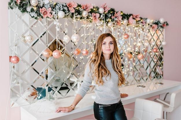 Het meisje, de vrouw thuis met versierd kerstbinnenland. vrolijk kerstfeest. het concept van gezinsvakantie in de winter.