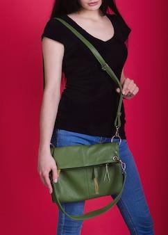 Het meisje demonstreert een elegante dames lederen handtas. prachtige vrouwelijke accessoire. damestas advertentie