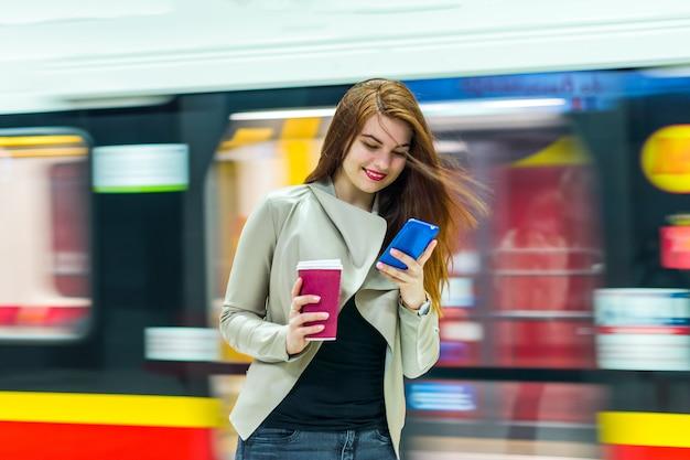 Het meisje dichtbij metro die de smartphone bekijken