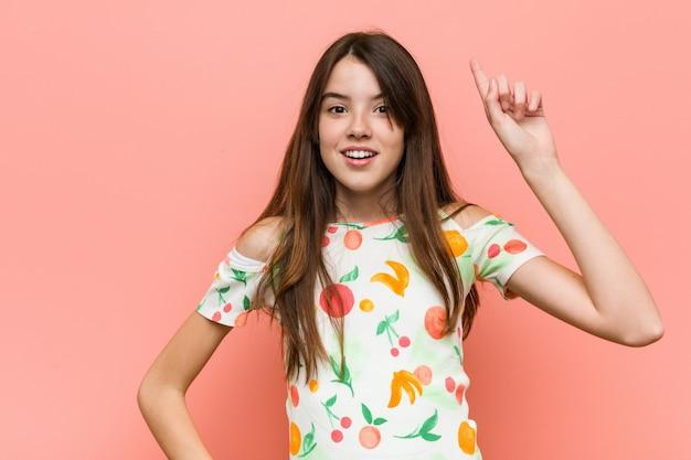 Het meisje die de zomer dragen kleedt zich tegen een muur die een idee, inspiratie hebben.