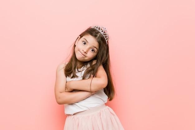 Het meisje die een prinses dragen kijkt het ongelukkige kijken in camera met sarcastische uitdrukking.