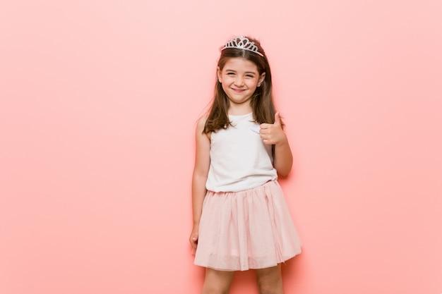 Het meisje die een prinses dragen kijkt omhoog glimlachend en duim opheffend