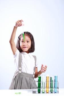 Het meisje die een reageerbuis met vloeistof houden, de wetenschapsschemie en het wetenschapsonderwijs bedriegen