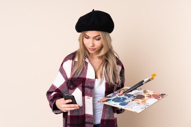 Het meisje die van de tienerkunstenaar een palet op de blauwe weg te nemen koffie van de muurholding en mobiel houden
