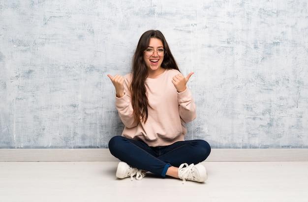 Het meisje die van de tienerstudent in een lijst met duimen op gebaar en het glimlachen bestuderen