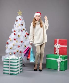 Het meisje die van vooraanzichtkerstmis met santahoed kleurrijke het winkelen zakken houden die haar linkerhand opheffen