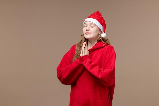 Het meisje die van vooraanzichtkerstmis op de bruine achtergrondvakantie modelkerstmis bidden