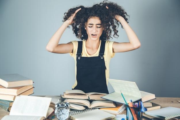 Het meisje dient haar met boeken op bureau in