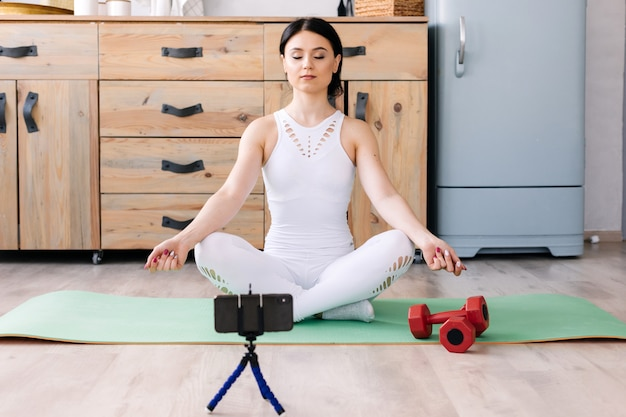 Het meisje doet binnen meditatie en oefeningen op mat