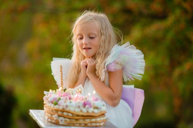 Het meisje doet een wens en blaast de kaarsen op de cake uit