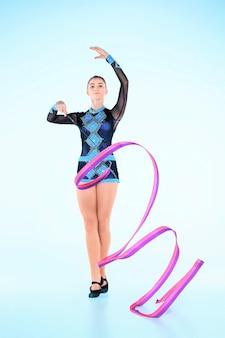 Het meisje doet gymnastiek dansen met gekleurd lint op een blauwe achtergrond
