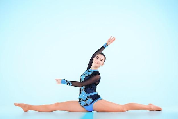 Het meisje doet gymnastiek dansen op een blauwe achtergrond