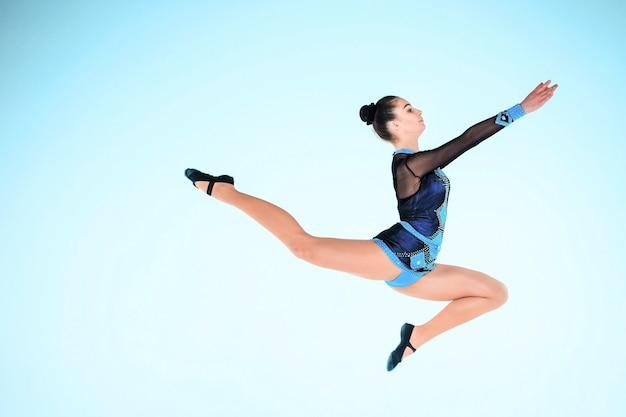 Het meisje doet gymnastiek dansen op een blauwe muur