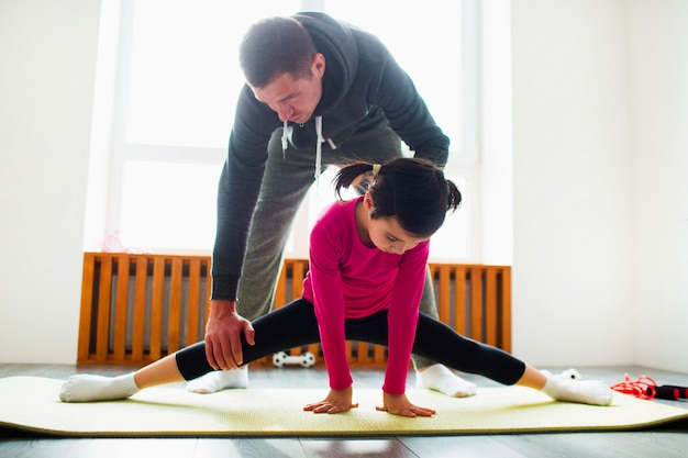 Het meisje doet thuis uitrekkende oefeningentraining. schattige jongen en papa trainen op een mat binnenshuis. klein donkerharig vrouwelijk model in sportkleding heeft oefeningen bij het raam in haar kamer