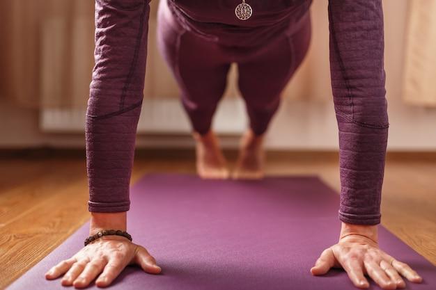 Het meisje doet yoga in de asana-stand op een lila mat. gezonde levensstijl, asana en meditatiepraktijken