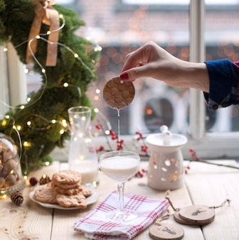 Het meisje doopt koekjes in melk in een glas bij een lijst bij het venster en een kroon van een kerstboom