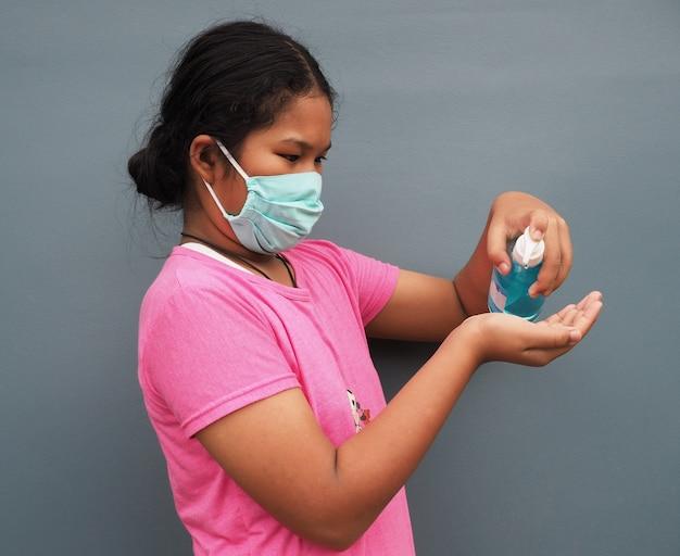 Het meisje draagt een beschermend masker en drukt op de alcoholgel om haar handen te wassen.