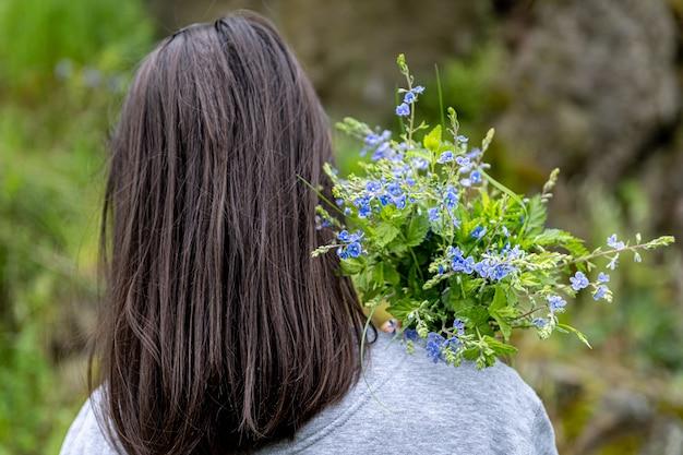 Het meisje draagt een boeket bloemen verzameld in het lentebos, uitzicht vanaf de achterkant.