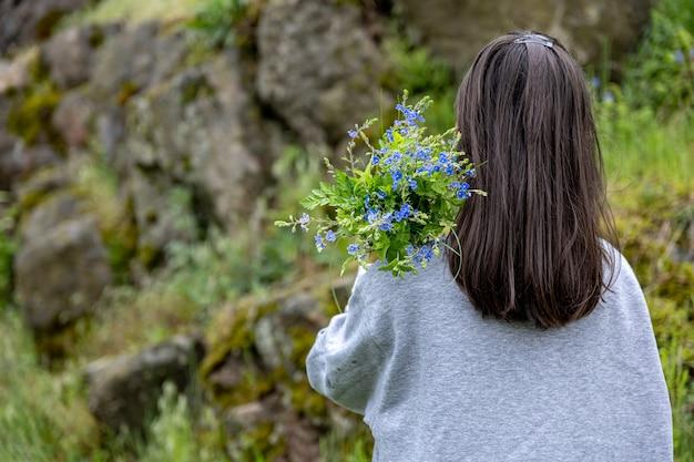 Het meisje draagt een boeket bloemen verzameld in het lentebos, uitzicht vanaf de achterkant