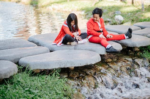 Het meisje draagt een zandige jurk en de jongen met een kerstoutfit speelt vrolijk op de steen.