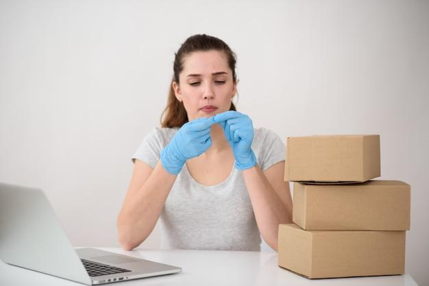 Het meisje draagt rubberhandschoenen vóór het werkzitting bij een lijst aangaande een lichte ruimte