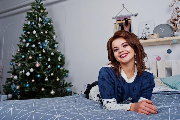 Het meisje draagt warme sweater liggend op het bed tegen nieuwe jaarboom met dozen op studio. gelukkig wintervakantie concept.
