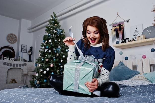 Het meisje draagt warme sweaterzitting op het bed tegen nieuwe jaarboom met stelt doos bij handen op studio voor. gelukkig wintervakantie concept.