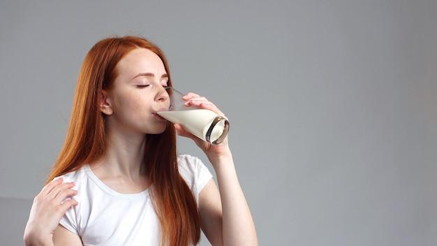 Het meisje drinkt een glas melk. een aantrekkelijke roodharige met een milkshake in haar hand. zuivel product. vrouw met een glas melk.