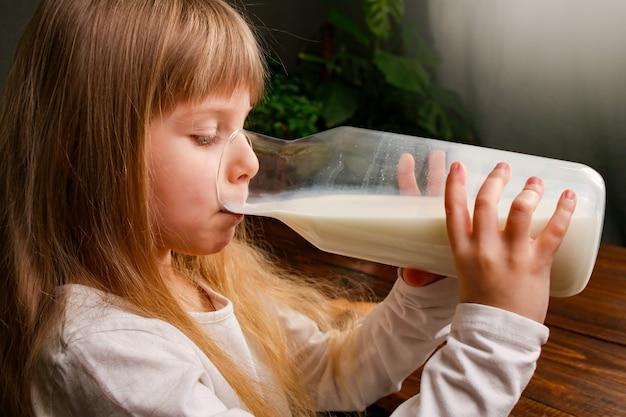 Het meisje drinkt gezonde zelfgemaakte melk uit een glazen kan