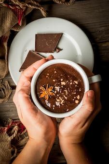 Het meisje drinkt hete chocolademok, met kerstmis huidig op rustieke lijst