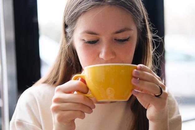 Het meisje drinkt koffie uit een gele mok en kijkt naar beneden.