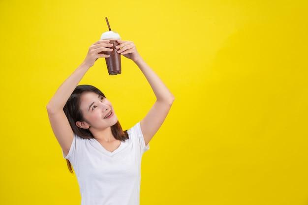 Het meisje drinkt koud water uit cacao uit een doorzichtig plastic glas op een gele.