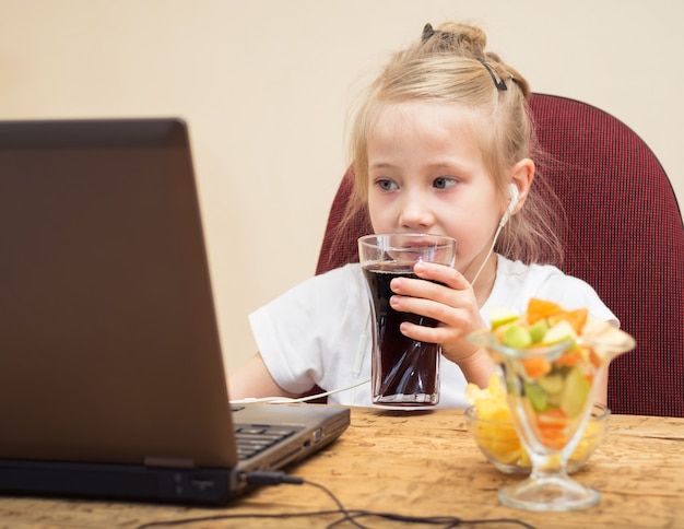Het meisje drinkt sodawater voor de computer.