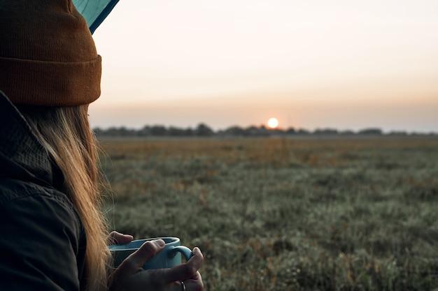 Het meisje drinkt uit een beker en kijkt naar de koude dageraad. reizen.