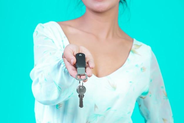 Het meisje droeg een wit shirt met lange mouwen en een bloemenpatroon met een sleutelhanger met een blauwe.