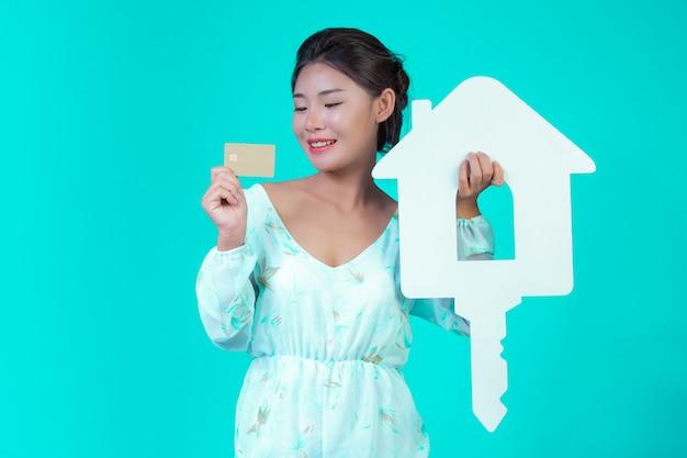 Het meisje droeg een wit shirt met lange mouwen en een bloemenpatroon, met een wit huissymbool en een gouden creditcard met een blauwe.